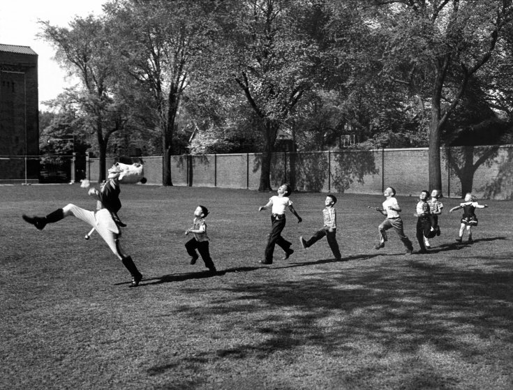 05897777.JPG - Uniformed drum major for the Univ. of MI marching band practicing his high-kicking prance as he leads a line of seven admiring children who are all trying to imitate his flamboyant technique while marching across the campus lawn.